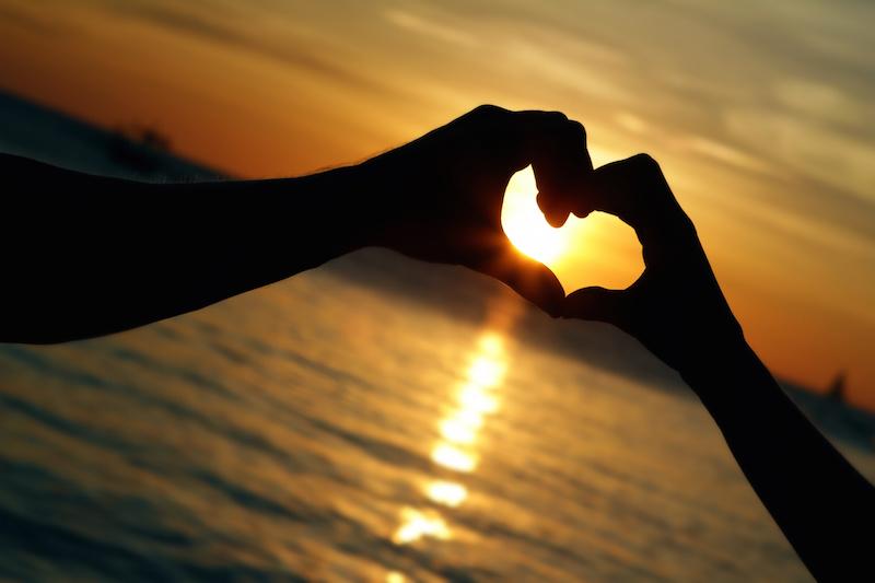 Hands make heart at sunset
