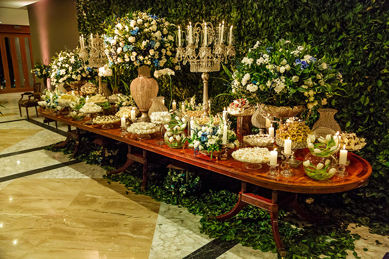 mesa de doces de casamento com muro verde