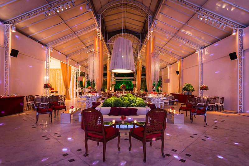 Decoração de casamento com lounges e arranjos vermelhos e verdes Madame Fiori