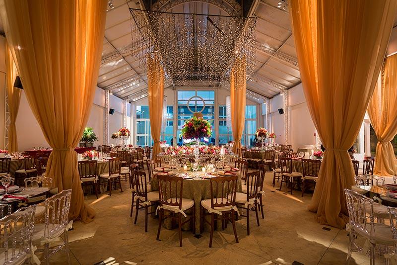 Decoração de casamento com luzes, velas, flores vermelhas e folhagens Madame Fiori