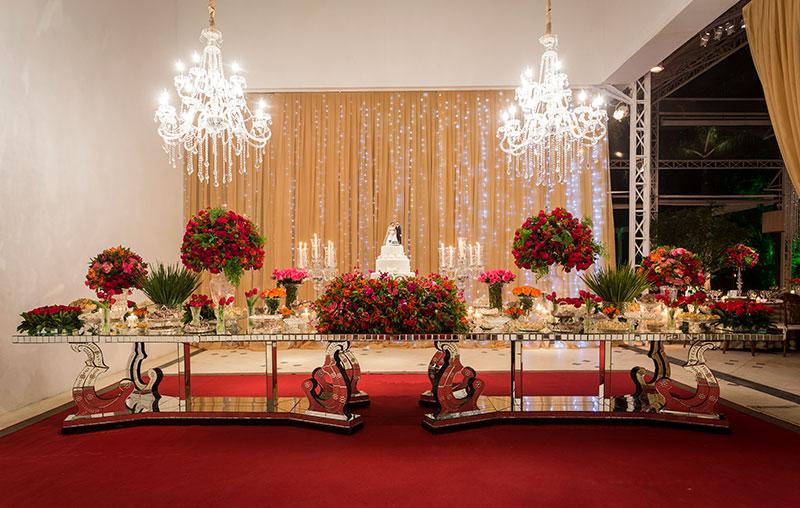 Mesa de doces de casamento com arranjo de flores vermelhas e verdes Madame Fiori