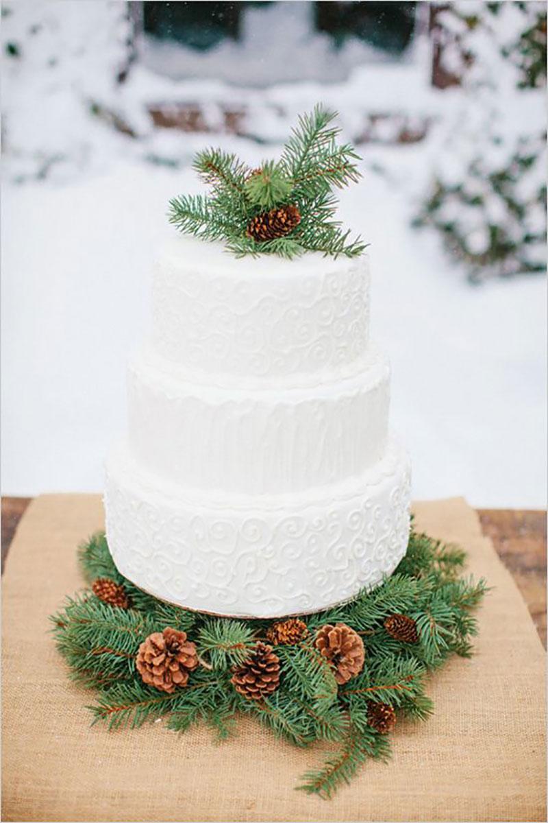 bolo de casamento com decoração de Natal com pinha e folhagens