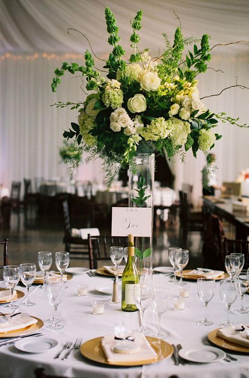 arranjo de mesa de convidados com flores brancas e folhagens greenery